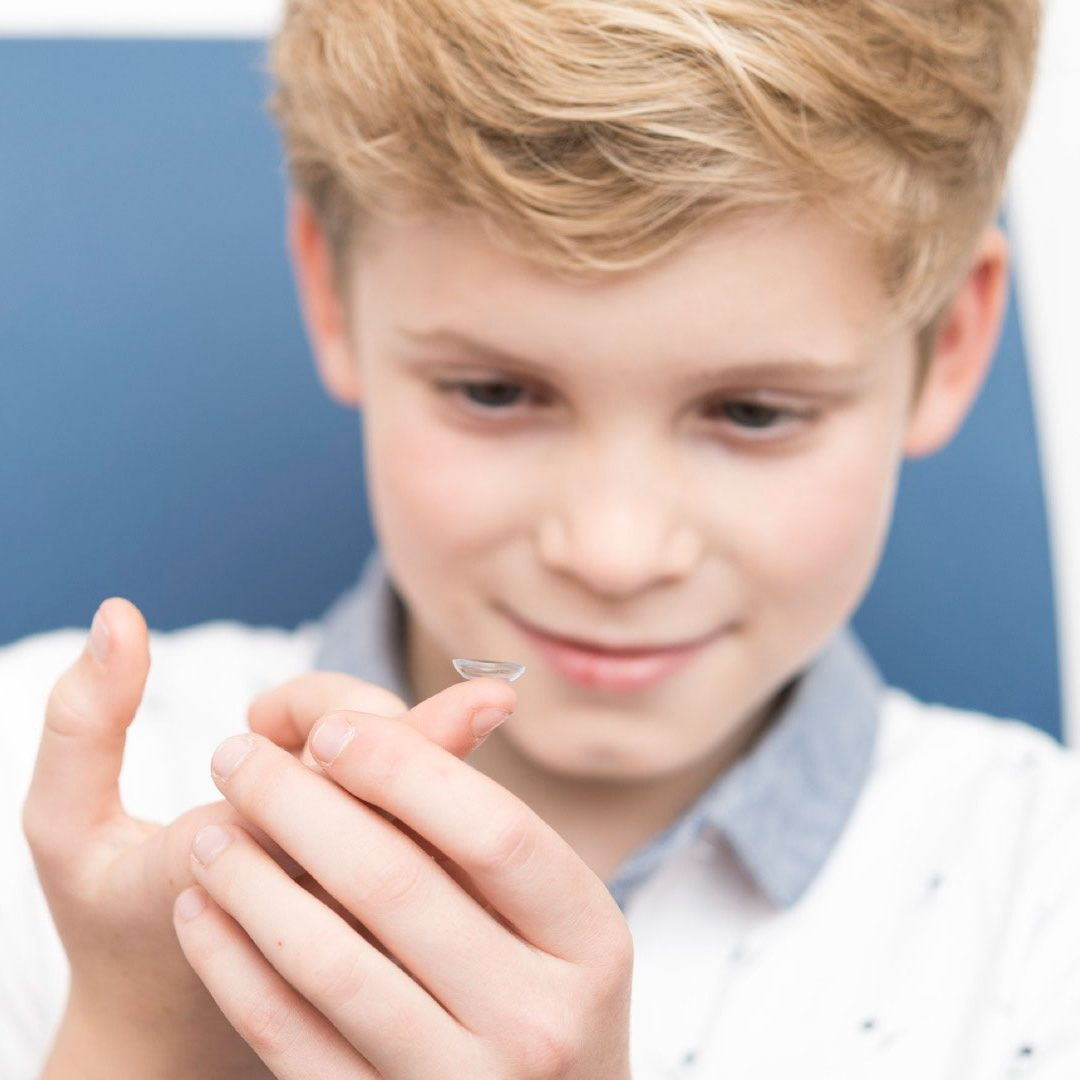 Child holding contact lens